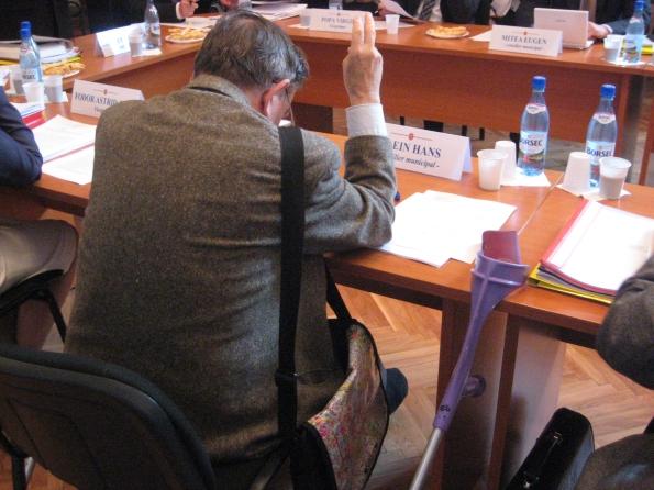 Hans Klein, pe vremea când era consilier. Veşnic cu mâna pe sus ca să aprobe proiectele şefului său de la FDGR, Klaus Iohannis. La Sibiu numai primarul propune proiecte de Hotărâri ale Consiliui Local, singurul rol al consilierilor fiind doar de maşină de vot care să mimeze democraţia